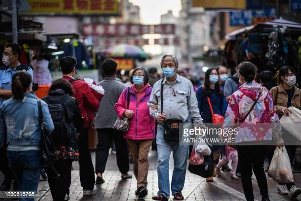 Pedestrians carry their shopping as they walk in the Sham Shui Po district of Kowloon in Hong Kong on January 27 one of the international business...