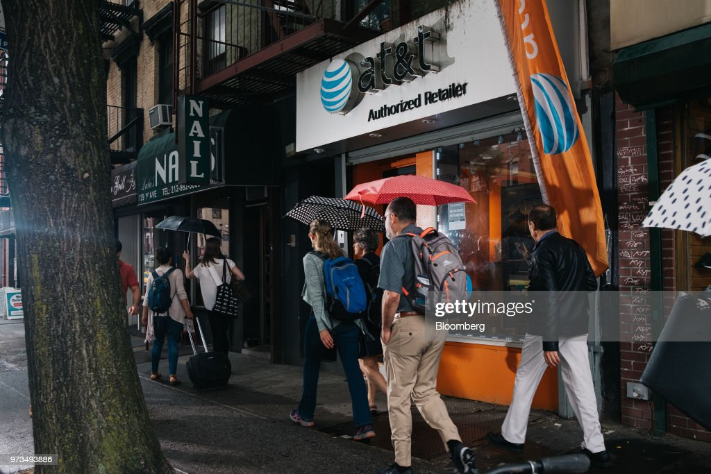 Pedestrians carry umbrellas while passing in front of an AT&T Inc. store location in New York, U.S., on Wednesday, June 13, 2018. AT&T Inc.'s sweeping court victory allowing its takeover of Time Warner Inc. delivers a sharp setback to the Justice Department's new approach to policing mergers under President Donald Trump and promises to spark a merger wave across industries. Photographer: Christopher Lee/Bloomberg via Getty Images