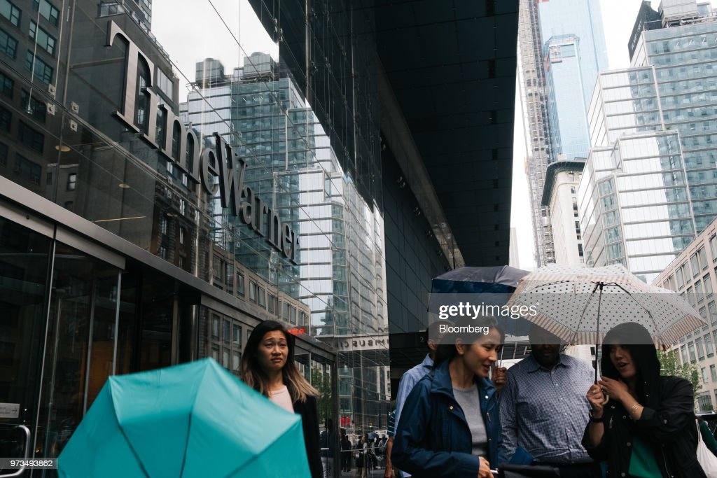 Pedestrians carry umbrellas while passing in front of the Time Warner Center in New York, U.S., on Wednesday, June 13, 2018. AT&T Inc.'s sweeping court victory allowing its takeover of Time Warner Inc. delivers a sharp setback to the Justice Department's new approach to policing mergers under President Donald Trump and promises to spark a merger wave across industries. Photographer: Christopher Lee/Bloomberg via Getty Images