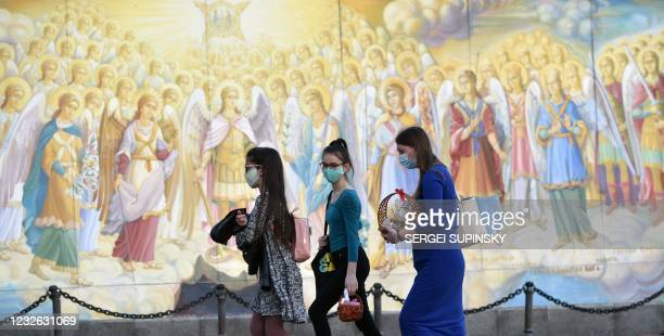 Pedestrians carrying Easter eggs and cakes walk past a religious mural outside Mykhaylo Gold Domes cathedral in Kiev on May 1, 2021.