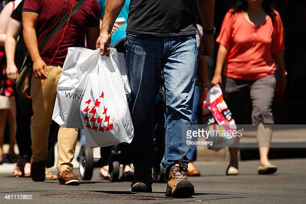 Pedestrians carrying shopping bags cross a road in the Chatswood retail area in Sydney Australia on Sunday Jan 4 2015 Australia's twospeed economy is...