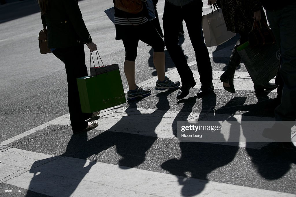 Pedestrians carrying shopping bags cross the street in the Georgetown neighborhood of Washington, D.C., U.S., on Saturday, March 9, 2013. The U.S. Census Bureau is expected to release advance retail sales data for February on March 13. Photographer: Andrew Harrer/Bloomberg via Getty Images