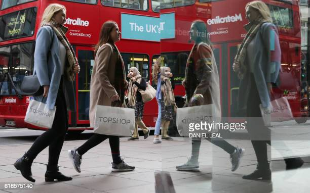 Pedestrians carrying shopping bags in Oxford Street in central London on October 27 2016 Britain's economy won a double boost on October 27 on news...