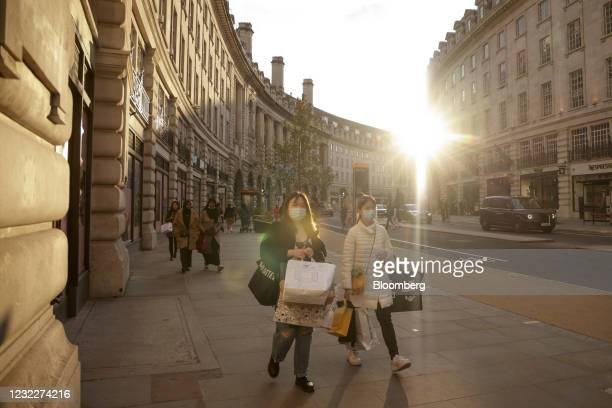 Pedestrians carrying shopping bags walk along Regent Street in London, U.K., on Monday, April 12, 2021. Consumers flocked to shopping streets across...