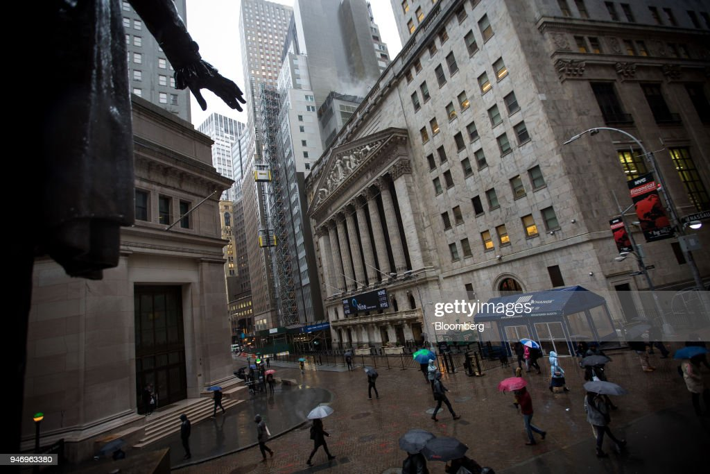 Pedestrians carrying umbrellas pass in front of the New York Stock Exchange (NYSE) in New York, U.S., on Monday, April 16, 2018. U.S. stocks rallied and Treasuries slid as geopolitical tensions eased and investors turned their attention to corporate results. Photographer: Michael Nagle/Bloomberg via Getty Images