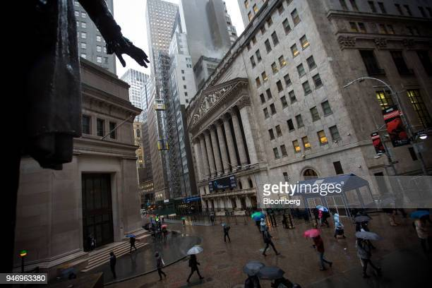 Pedestrians carrying umbrellas pass in front of the New York Stock Exchange in New York US on Monday April 16 2018 US stocks rallied and Treasuries...