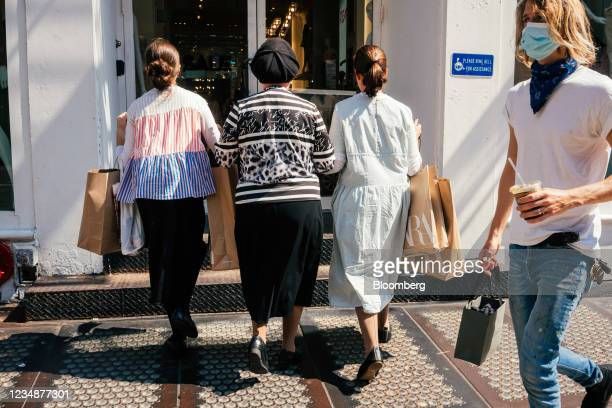 Pedestrians carrying Zara shopping bags enter a clothing store in the SoHo neighborhood of New York, U.S., on Wednesday, Aug. 25, 2021. Consumer...