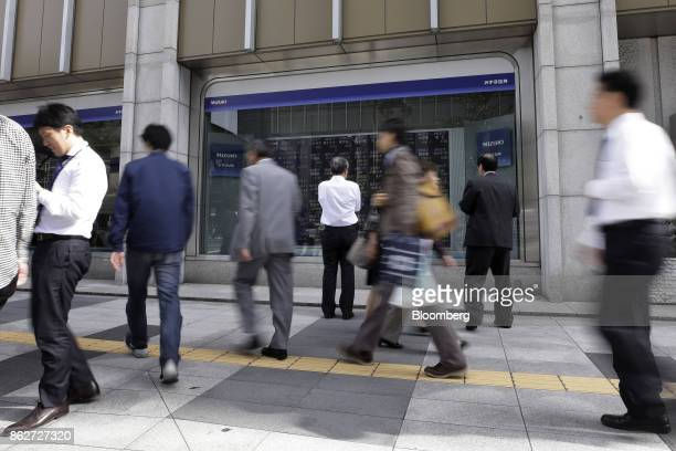 Pedestrians center look at an electronic stock board while other people walk by outside a securities firm in Tokyo Japan on Wednesday Oct 18 2017 As...
