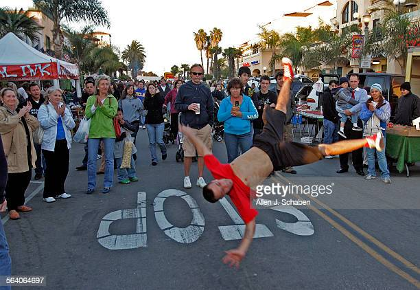 Pedestrians cheer for Phillip 'Spee–d' Albuquerque of Los Angeles performs B–Boying/Breakdancing with his group Infamous Squad on Main Street Tuesday...