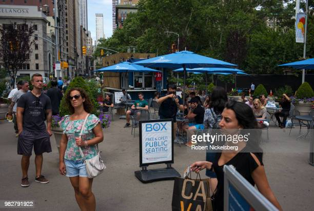 Pedestrians congregate in Madison Square June 20 2018 in midtown New York City