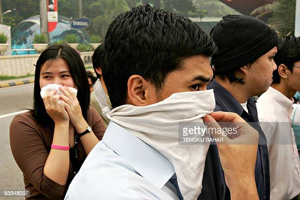 Pedestrians cover their faces with handkerchiefs to aid breathing in dense haze in downtown Kuala Lumpur 10 August 2005 Malaysia announced it would...