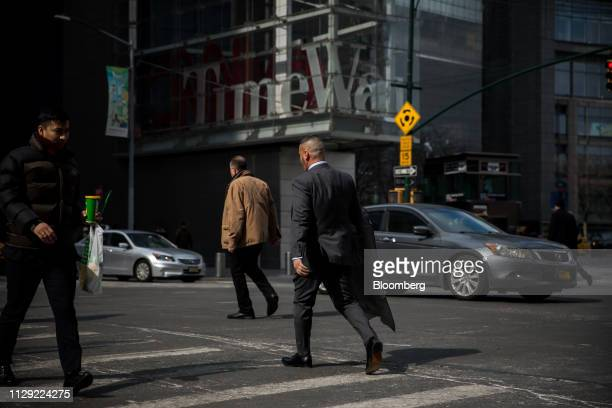 Pedestrians cross 8th Avenue in front of the Time Warner Center in New York, U.S., on Thursday, March 7, 2019. U.S. Stocks dropped with the dollar...