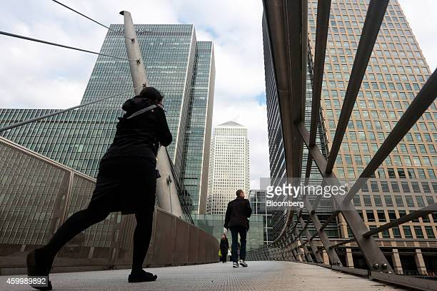 Pedestrians cross a bridge near the offices of JPMorgan Chase Co left and the One Canada Square office building center in the Canary Wharf business...