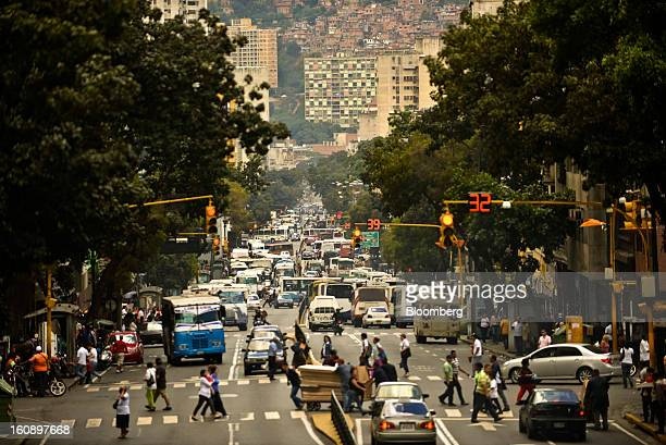 Pedestrians cross a busy street in downtown Caracas Venezuela on Monday Jan 14 2013 Venezuela's central bank is considering ways to expand the supply...