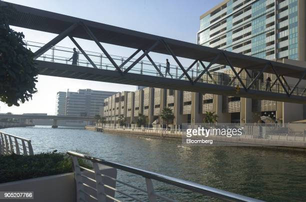Pedestrians cross a footbridge across a waterway in the Al Muneera gated enclave developed by Carillion Plc and AlFuttaim Group along the Al Raha...