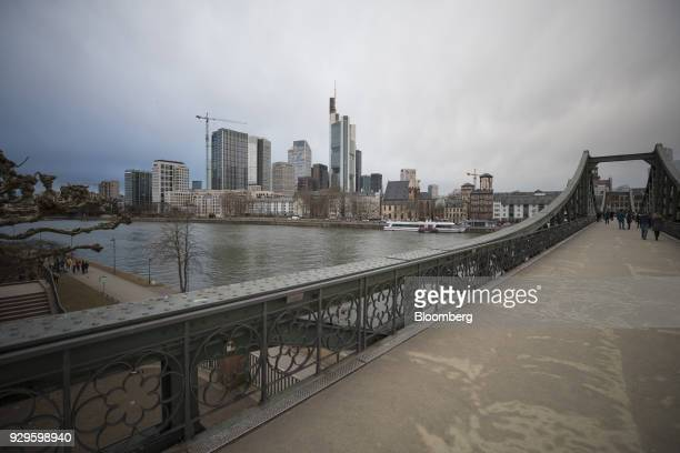 Pedestrians cross a footbridge spanning the River Main as skyscrapers stand in the financial district beyond in Frankfurt Germany on Thursday March 8...