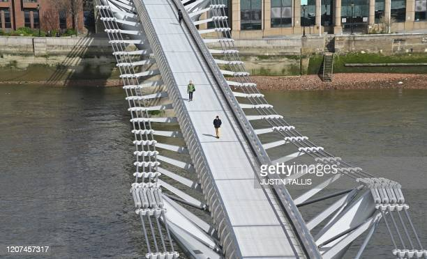 TOPSHOT Pedestrians cross a quiet Millennium Footbridge across the River Thames in London in the midmorning on March 17 2020 after the UK government...