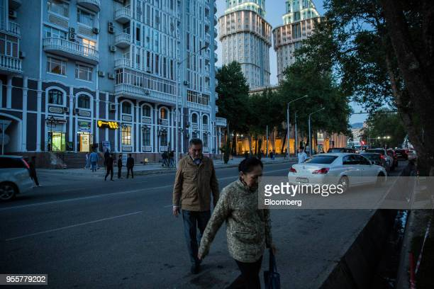Pedestrians cross a road as commercial and residential buildings stand in Dushanbe Tajikistan on Saturday April 21 2018 Flung into independence after...