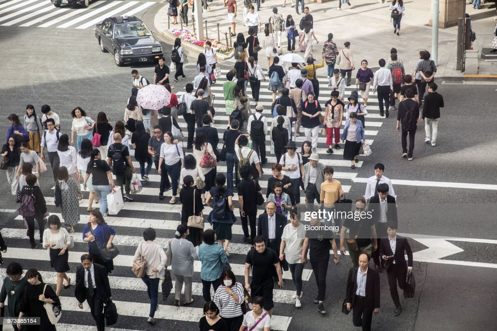Pedestrians cross a road Ginza district of Tokyo, Japan, on Friday, May 25, 2018. The savings-rich elderly spend about 9.7 trillion yen ($87 billion) a year on their offspring and such spending last year accounted for about a third of the modest growth in total consumption, according to Hiromichi Shirakawa, chief Japan economist at Credit Suisse Group. Photographer: Shiho Fukada/Bloomberg via Getty Images