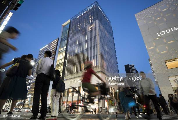 Pedestrians cross a road in front of a Bulgari SpA store center at night in the Ginza area of Tokyo Japan on Tuesday Aug 21 2018 Japan is scheduled...