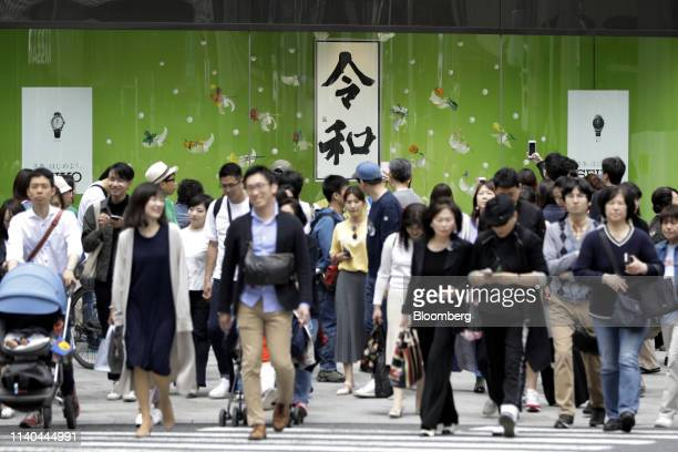 Pedestrians cross a road in front of a calligraphy work showing the name of Japan's new imperial era Reiwa center displayed in the window of a...