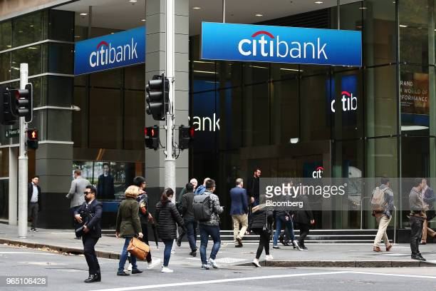 Pedestrians cross a road in front of a Citigroup Inc Citibank branch in Sydney Australia on Friday June 1 2018 Australia's banking industry faces an...