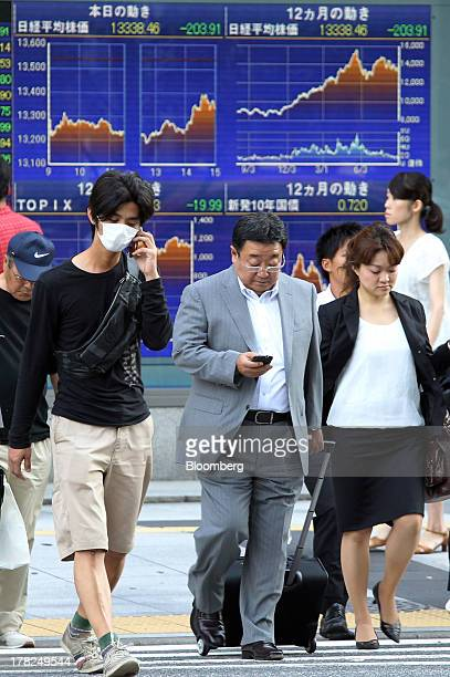 Pedestrians cross a road in front of an electronic monitor outside a securities firm in Tokyo Japan on Wednesday Aug 28 2013 Japanese shares declined...
