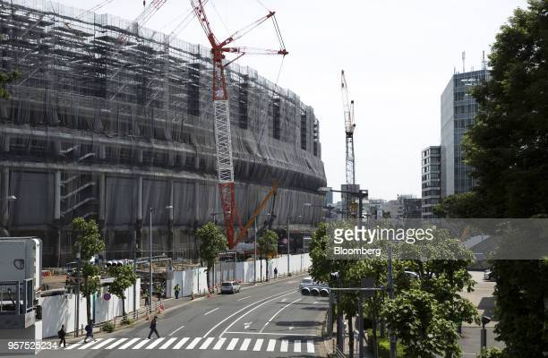 Pedestrians cross a road in front of the construction site of the New National Stadium a venue for 2020 Summer Olympics and Paralympics in Tokyo...
