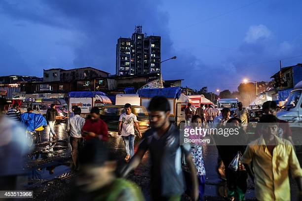 Pedestrians cross a road in the Dharavi slum area of Mumbai India on Monday Aug 11 2014 Almost a year after Reserve Bank of India Governor Raghuram...