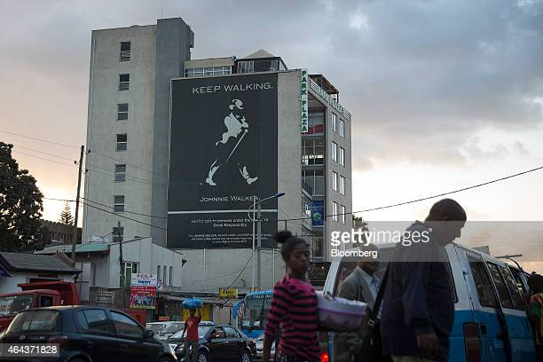 Pedestrians cross a road near a giant billboard advertising the Johnnie Walker whiskey brand owned by Diageo Plc in Addis Ababa Ethiopia on Tuesday...