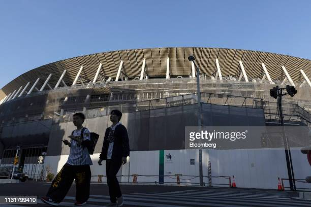 Pedestrians cross a road near the construction site of the New National Stadium the main venue for the Tokyo 2020 Olympic and Paralympic Games in...