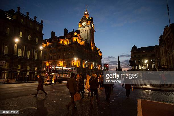 Pedestrians cross a road near the illuminated clock tower of the Balmoral Hotel center on Princes Street in Edinburgh UK on Wednesday Jan 29 2014...