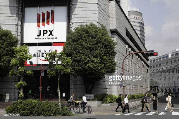 Pedestrians cross a road near the Tokyo Stock Exchange operated by Japan Exchange Group Inc in Tokyo Japan on Wednesday Aug 30 2017 Equity indexes in...