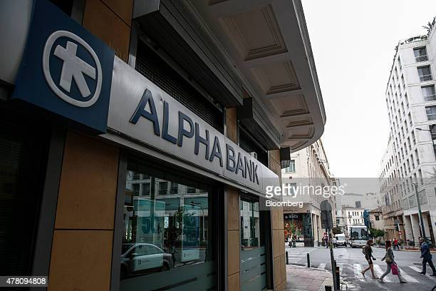 Pedestrians cross a road outside an Alpha Bank AE bank branch in Athens Greece on Monday June 22 2015 Dutch Finance Minister Jeroen Dijsselbloem who...