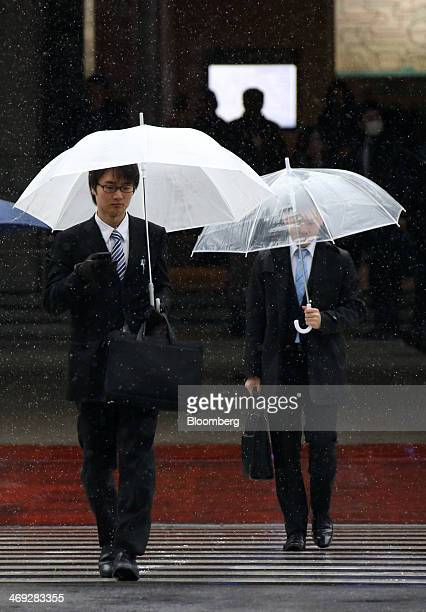 Pedestrians cross a road while carrying umbrellas as snow falls in Tokyo Japan on Friday Feb 14 2014 Snowfall in Tokyo disrupted train and plane...