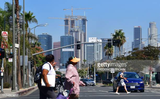 Pedestrians cross a street against a backdrop of luxury highrise apartments under construction in Los Angeles, California on October 8, 2019. -...