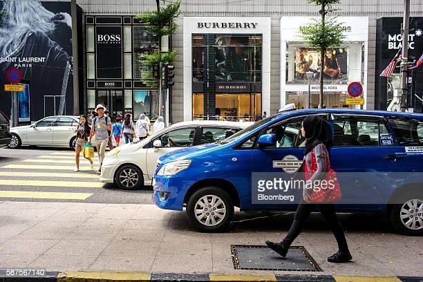 Pedestrians cross a street as a woman walks along a pavement in Kuala Lumpur Malaysia on Friday Aug 5 2016 Malaysia's secondquarter gross domestic...