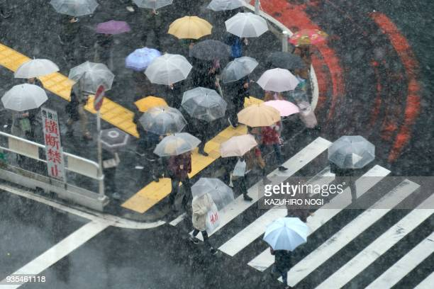 TOPSHOT Pedestrians cross a street as it snows in Tokyo on March 21 2018 / AFP PHOTO / Kazuhiro NOGI