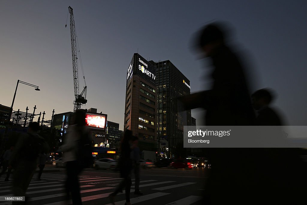 Pedestrians cross a street at dusk as a Samsung Electronics Co. advertisement is illuminated in the background at Gwanghwamun Square in Seoul, South Korea, on Tuesday, Oct. 22, 2013. Samsung Electronics is scheduled to release third-quarter earnings on Oct. 25. Photographer: SeongJoon Cho/Bloomberg via Getty Images