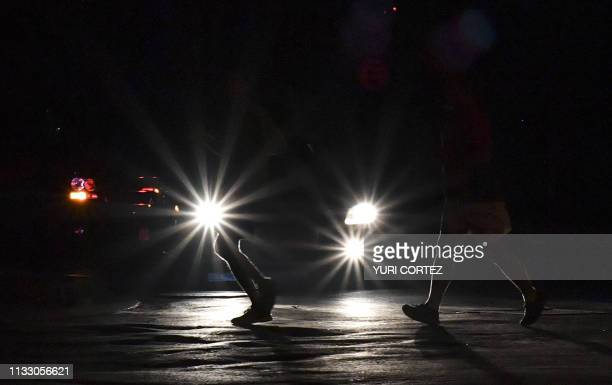 TOPSHOT Pedestrians cross a street during a power outage in Caracas Venezuela on March 26 two weeks after a similar outage caused deaths and chaos...