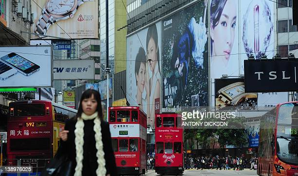 STORY 'HONG KONGECONOMYBUDGETTAX' BY Pedestrians cross a street in a shopping district in Hong Kong on February 13 2012 Hong Kong's competitiveness...