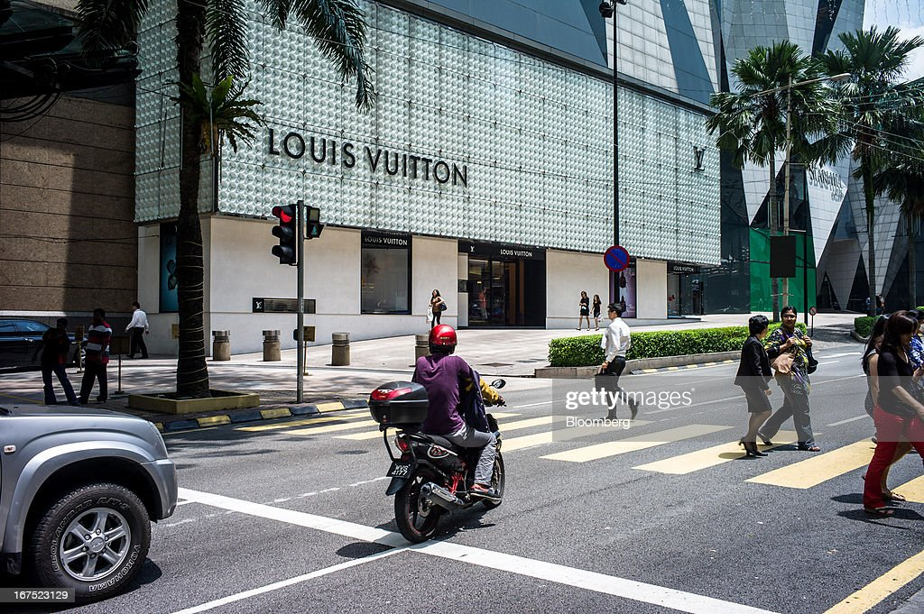 Pedestrians cross a street in front of a Louis Vuitton store, operated by LVMH Moet Hennessy Louis Vuitton SA, in Kuala Lumpur, Malaysia, on Thursday, April 25, 2013. Malaysians will go to the polls on May 5. Prime Minister Najib Razak's National Front coalition is seeking to extend its 55 years of unbroken rule in the face of a resurgent opposition led by Anwar Ibrahim. Photographer: Sanjit Das/Bloomberg via Getty Images