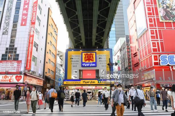 Pedestrians cross a street in front of a Matsumotokiyoshi Co. Store built under railway tracks in Tokyo, Japan, on Thursday, Sept. 3, 2020. In Tokyo,...
