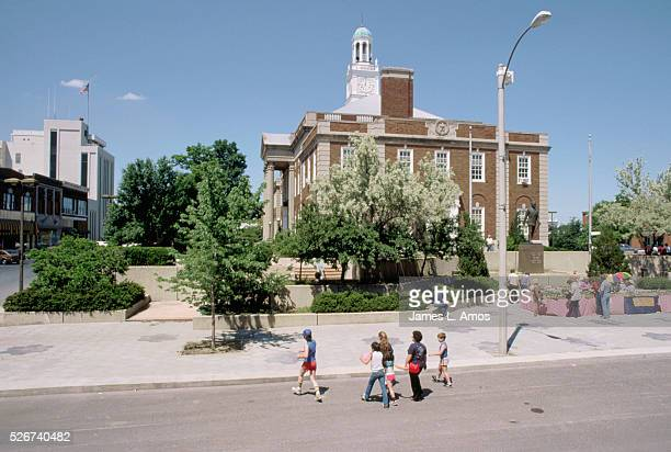 Pedestrians cross a street in front of the courthouse in a town where pioneers on the Oregon Trail bought supplies before their journey west on the...