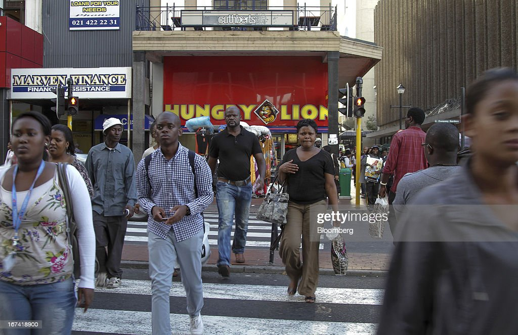 Pedestrians cross a street in the financial district of Cape Town, South Africa, on Wednesday, April 24, 2013. South Africa's gross domestic product is forecast to expand 2.6 percent this year, compared with 2.5 percent in 2012, according to the country's central bank. Photographer: Nadine Hutton/Bloomberg via Getty Images
