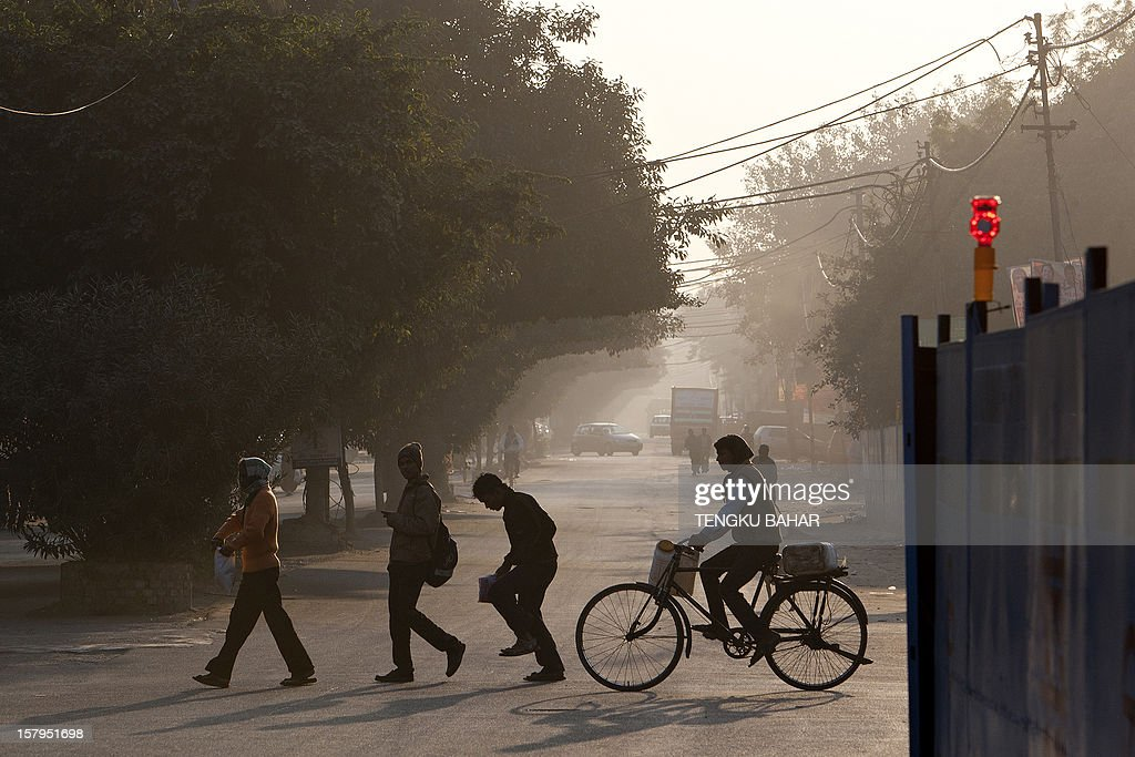 Pedestrians cross a street near a retail market area in New Delhi on December 8, 2012. India has long been criticised as one Asia's most inefficient bureaucracies, with its byzantine regulations and widespread corruption seen as a major deterrent to foreign investment.