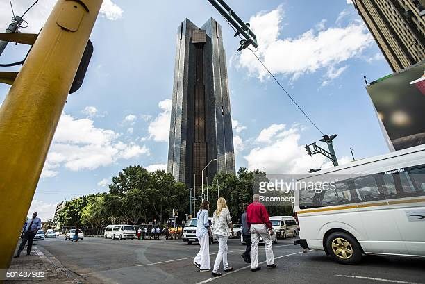 Pedestrians cross a street near the headquarters of the South African Reserve Bank center in the central business district in Pretoria South Africa...