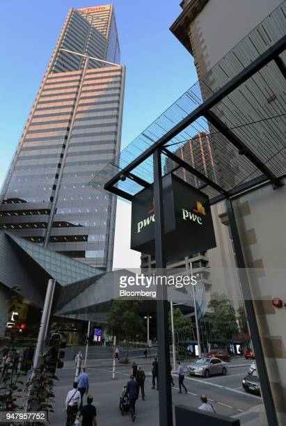 Pedestrians cross an intersection as signage for Pricewaterhouse Coopers International Ltd is displayed in the central business district of Perth...