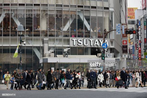 Pedestrians cross an intersection in front of a Tsutaya Corp shopping center in the Shibuya district of Tokyo Japan on Friday March 31 2017 The yen...