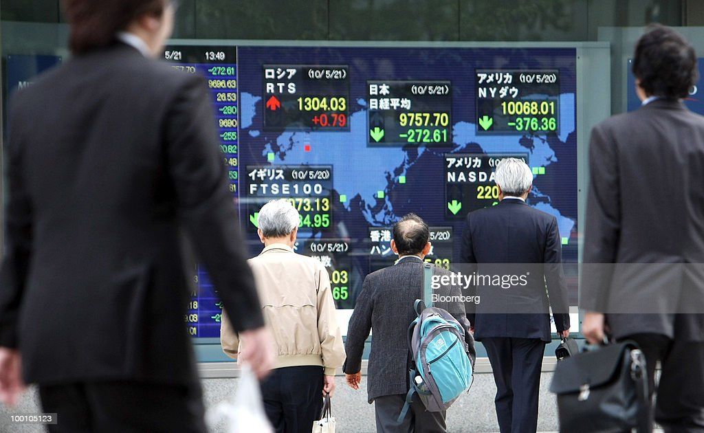 Pedestrians cross an intersection in front of an electronic stock board outside a securities firm in Tokyo, Japan, on Friday, May 21, 2010. Japanese stocks fell, putting key indexes on course for their biggest weekly drops in more than a year, as rising U.S. unemployment and a deepening split in Europe spurred concern the global economic recovery will stall. Photographer: Tomohiro Ohsumi/Bloomberg via Getty Images